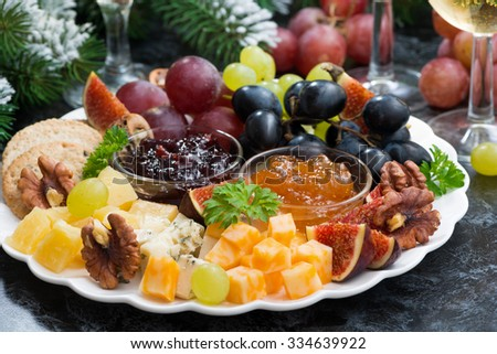 appetizers to the holiday - cheeses, fruits and jams, closeup, horizontal - stock photo