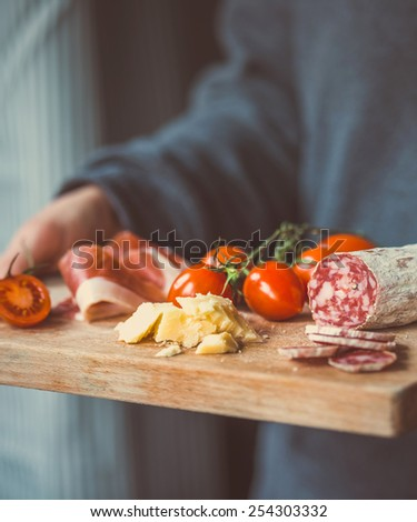 Appetizers - tomato, meat and cheese - on wooden board in hands. Toned image - stock photo