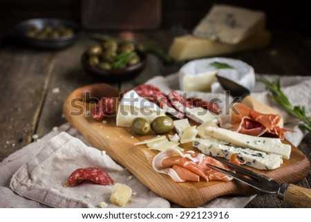 Appetizers. Various types of cheese, salami and prosciutto on  wooden cutting board, rustic background - stock photo