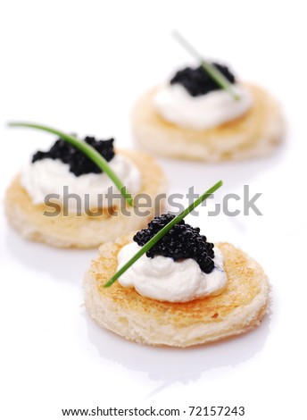 Appetizers with caviar on white - stock photo
