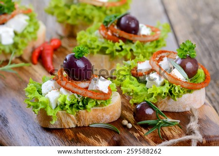 Appetizers with feta cheese and black olives - stock photo