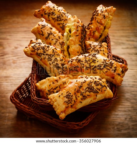 Appetizers with puff pastry stuffed with vegetables sprinkled with caraway seeds on a wooden table - stock photo