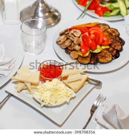 Appetizers with red caviar, pickles on a festive table in restaurant - stock photo