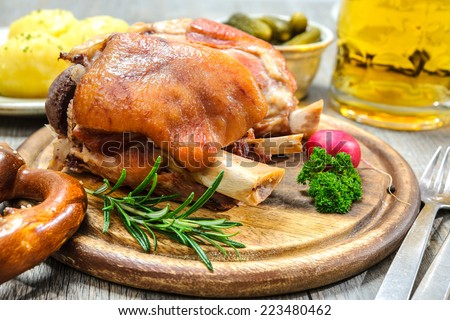 Appetizing Bavarian roast pork knuckle on cutting board - stock photo