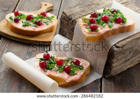 Appetizing bruschetta with salmon butter, capelin caviar, cranberry and herbs on a thick wooden board, paper, rustic - stock photo