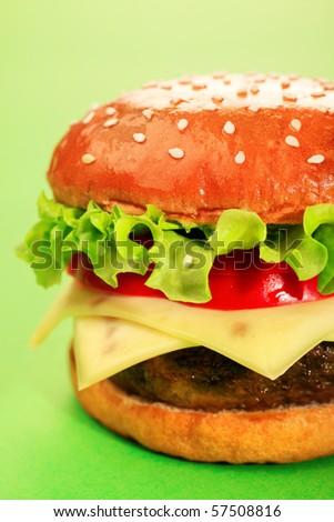 Appetizing cheeseburger over green background. - stock photo