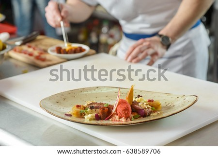 Appetizing exquisite dish, close-up. Chef wearing uniform on the background. French cuisine.