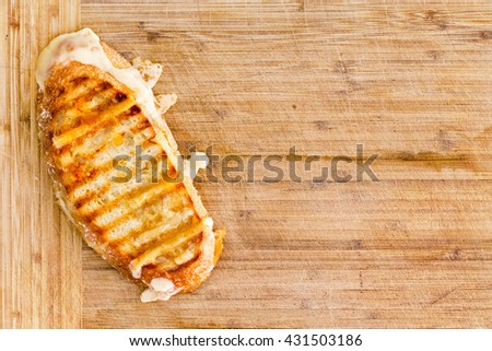 Appetizing grilled Italian panini bread cheese sandwich with melting cheese on a bamboo cutting board with copy space, overhead view
