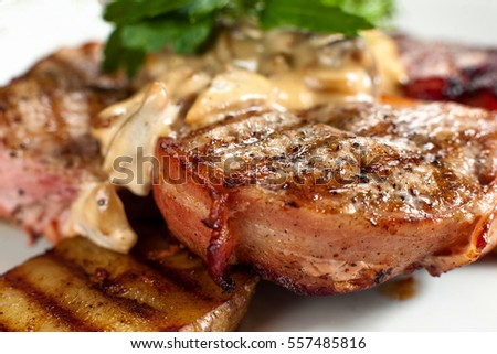 Appetizing grilled steak closeup side view. Juicy barbecue pork steak with potato and sauce. Meat meal background. Dining, junk food, restaurant menu concept