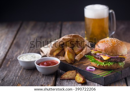 Appetizing homemade burger with beef patty, lettuce, tomato, cheese, pickled cucumbers and red onion served with fried potato, white sauce and ketchup, on wooden cutting board. With mug of light beer - stock photo