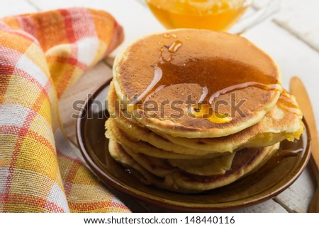 Appetizing pancakes on plate with honey/syrup on white table. Healthy breakfast. Selective focus. - stock photo