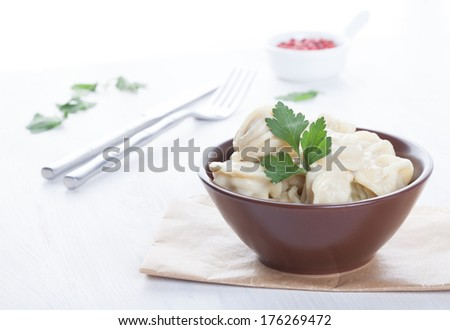 appetizing pelmeni in a brown bowl with sauce and spices - stock photo