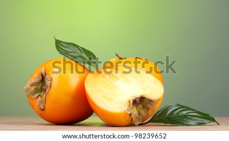 Appetizing persimmons on wooden table on green background - stock photo
