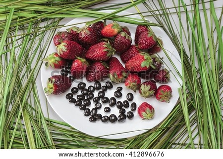 Appetizing picture of strawberries laid out on the grass and a white plate - stock photo