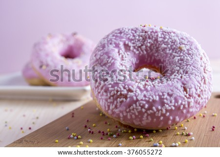 Appetizing pink donuts sprinkled with confetti on table. Close-up - stock photo