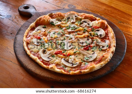 Appetizing pizza with mushrooms on a wooden tray - stock photo