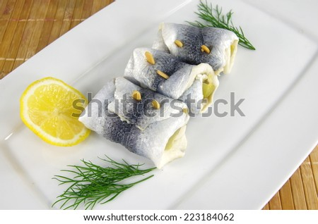 appetizing rollmop with lemon and dill   - stock photo