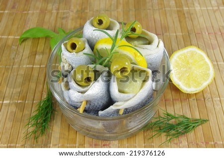 appetizing rollmop with lemon rosemary and olive  - stock photo