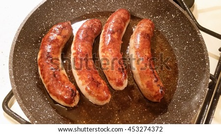 Appetizing ruddy juicy sausages fried in a large frying pan - stock photo