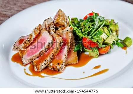 Appetizing slightly roasted tuna with grilled vegetables closeup shot - stock photo