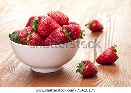 Appetizing strawberry in the bowl. Isolated on a white background. - stock photo