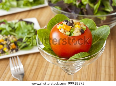 Appetizing tomato stuffed with quinoa salad and greens - stock photo