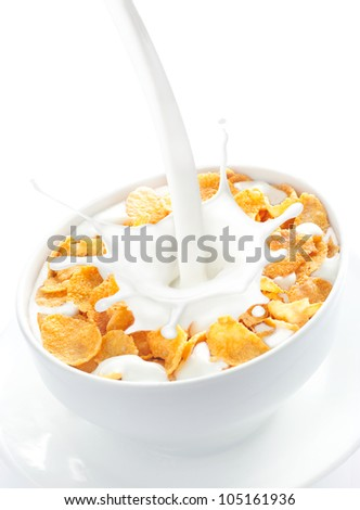 Appetizing view of milk pouring into a bowl of nutritious and delicious corn flake cereal - stock photo