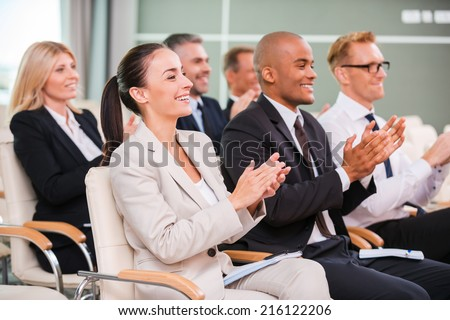 Applauding to speaker. Group of happy business people in formalwear sitting at the chairs in conference hall and applauding  - stock photo