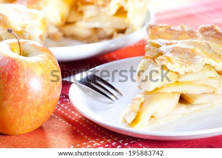 apple and apple pie on red tablecloth, shallow dof - stock photo