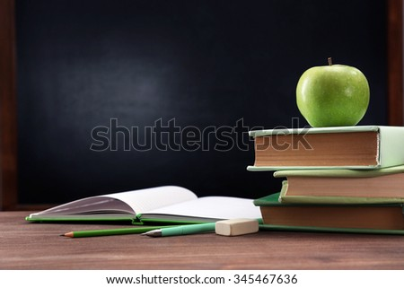Apple and books on desk background