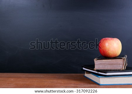 Apple and Books on the wooden desk with Blackboard Background.