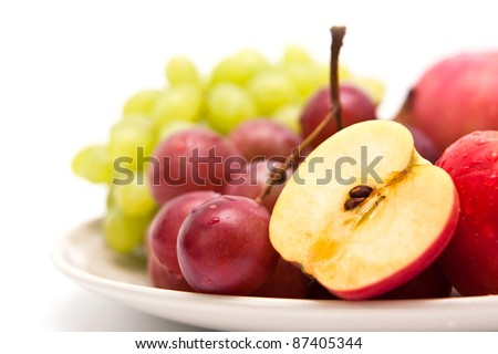 Apple and grape fruit on dish, isolate on white background