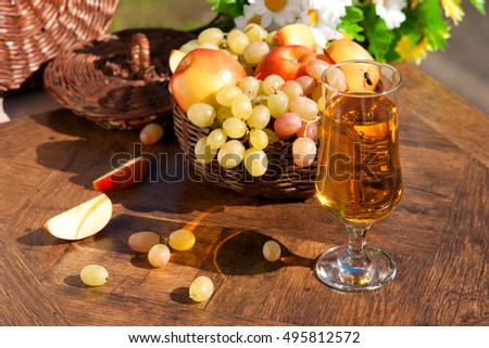 Apple and grape juice under the bright sun. Near the juice are apples and grapes. Bee sitting on a glass of juice. Juice, apples and grapes appetizing look and bright.