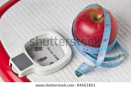 apple and measuring tape on the floor scales isolated on white - stock photo