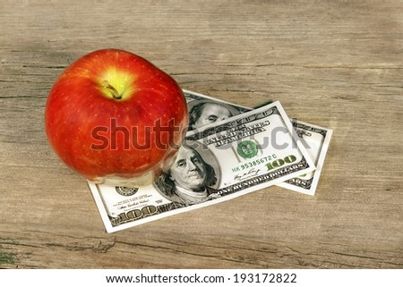 Apple and Money on grunge wood board - stock photo