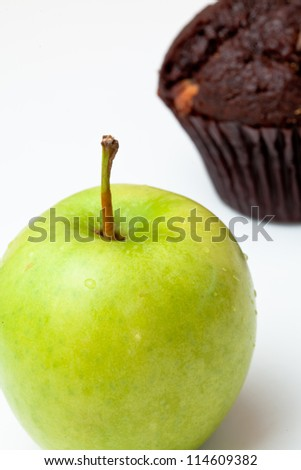 Apple and muffin against a white background