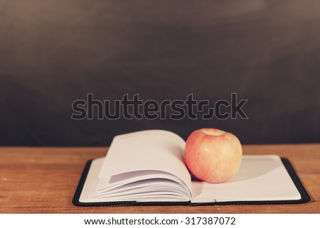 Apple and opened book on the wooden desk with blackboard background. - stock photo