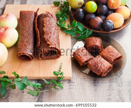 Apple and plum fruit leather rolls. Fruit candy - pastille. Healthy snack. Top view. Fresh summer fruits. Plum, apples and peach on wooden table.