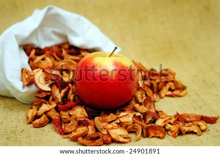 Apple and pocket of dessicated apples on the flax background - stock photo