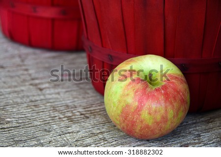 apple and red bushel basket on weathered wood at the market - stock photo
