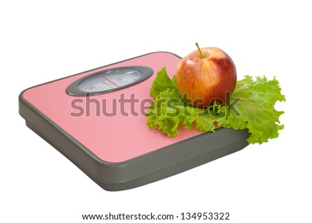 Apple and salad lie on the floor scales