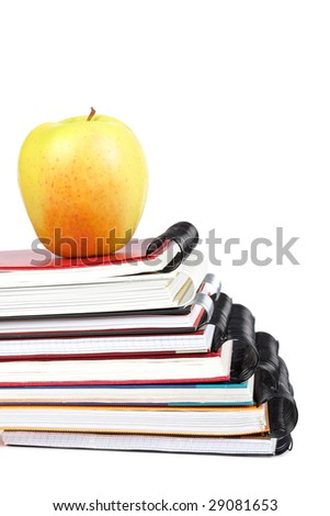 Apple and some notebooks with soft shadow on white background. Shallow depth of field - stock photo