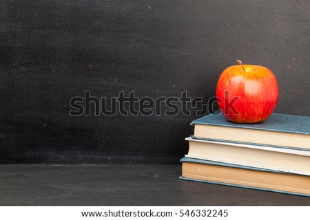 Apple And Stack Of Books On Chalkboard Background With Copy Space