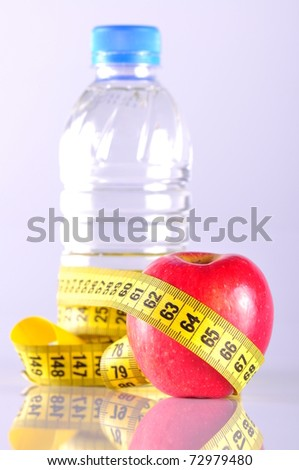 apple and water bottle surrounded by measurement
