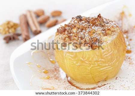 Apple baked with cottage cheese and raisins, decorated with nuts, cinnamon and powdered sugar - stock photo