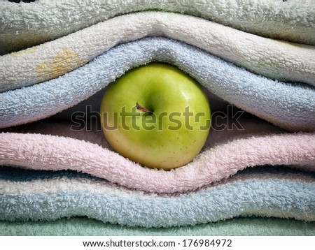 Apple between clean towels as the concept of cleanliness. - stock photo