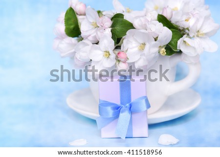 Apple blossom flowers in cup with gift box - stock photo