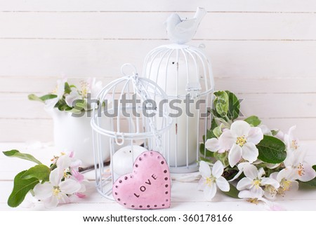 Apple blossom,  two decorative hearts, old books  on white painted wooden planks. Selective focus is on apple blossom.  - stock photo