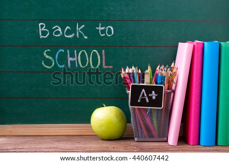 Apple, books and colored pencils on the chalkboard with back to school written background