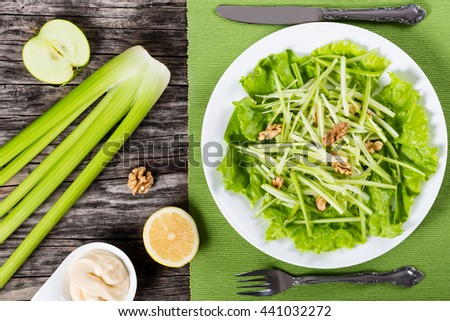apple, celery and walnut salad on a white dish on a table napkin with fork and knife, simply and easy recipe, ingredients on a wooden background, view from above - stock photo